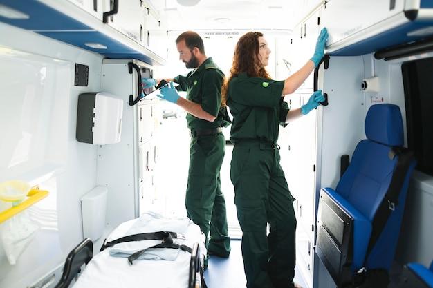 Sanitäter-team, das ausrüstung in einem krankenwagen überprüft