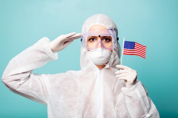 Sanitäterfrau, die schutzkleidung gegen das virus mit flagge der vereinigten staaten von amerika auf einem blauen hintergrund trägt