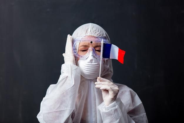 Sanitäterfrau, die schutzkleidung gegen das virus mit frankreich-flagge trägt