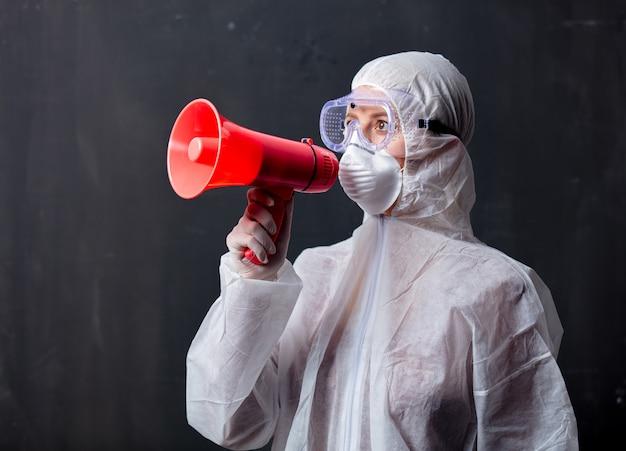 Sanitäterfrau, die schutzkleidung gegen das virus mit megaphon trägt