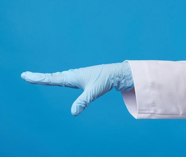 Sanitäterin im weißen kittel, in blauen sterilen handschuhen tragend