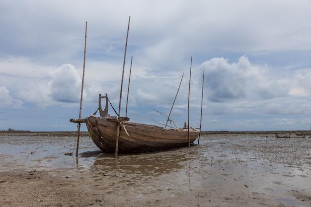 Sank fischerboot am sandstrand und schlamm