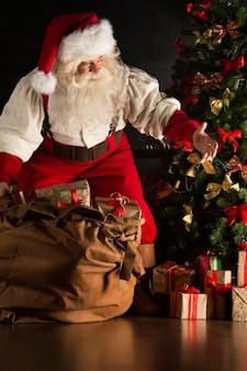 Sankt, die geschenke unter weihnachtsbaum in der dunkelkammer einsetzt