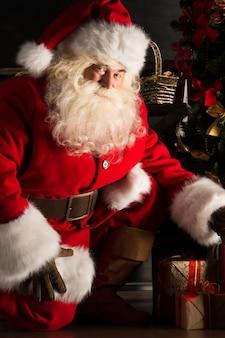Sankt, die geschenke unter weihnachtsbaum in der dunkelkammer setzt