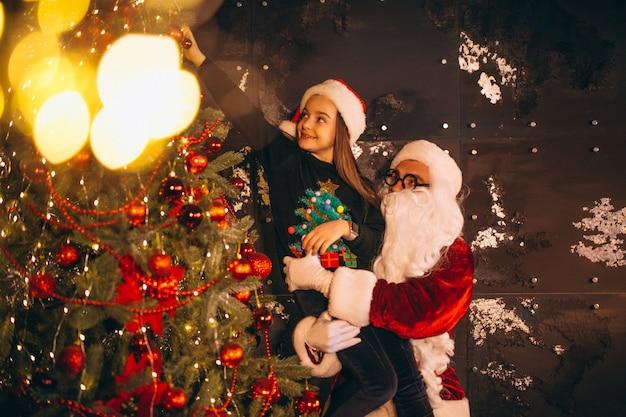Sankt mit dem kleinen mädchen, das zusammen weihnachtsbaum verziert