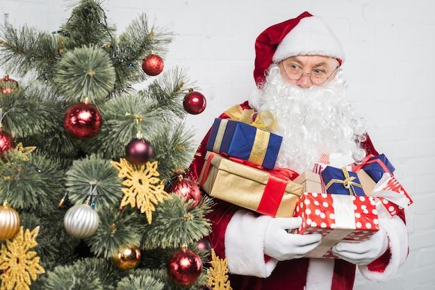Sankt mit geschenkboxen in händen nahe verziertem weihnachtsbaum