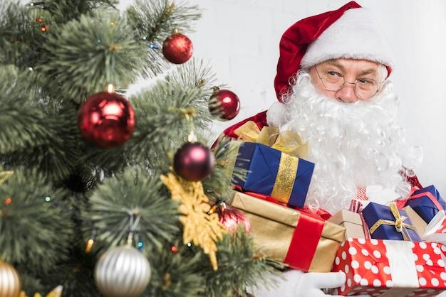 Sankt mit geschenken in den händen nahe verziertem weihnachtsbaum