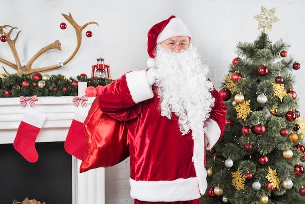 Sankt mit großem sack geschenken nähern sich weihnachtsbaum
