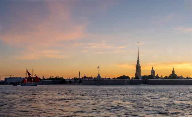 Sankt petersburg. russland. die untergehende sonne scheint durch die segel eines schiffes auf der newa. segelboot bei sonnenuntergang. die brigantine segelt in der nähe der peter-und-paul-festung. scharlachrotes segel. petersburger tradition.