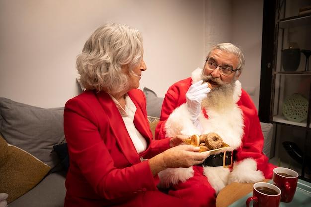 Sankt und frau, die weihnachtsplätzchen essen