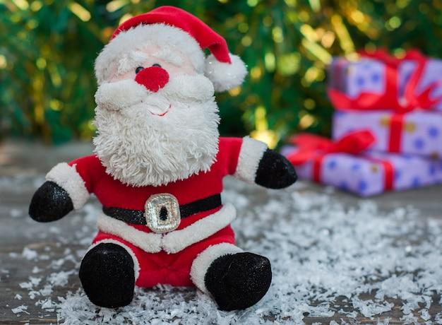 Santa claus auf einer grauen holzoberfläche mit schnee