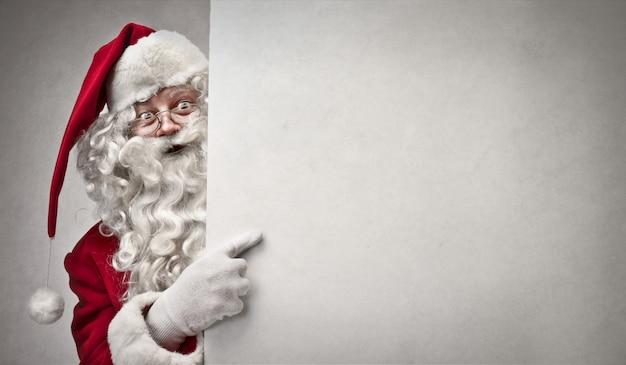 Santa claus, die auf ein brett zeigt