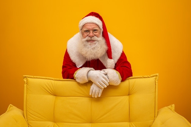 Santa claus, die auf einer gelben couch auf gelb sitzt