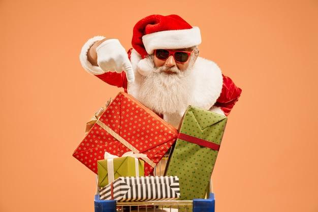 Santa claus, die auf präsentkartons in der einkaufslaufkatze zeigt