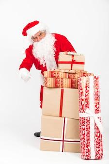 Santa claus, die auf stapel weihnachtsgeschenke zeigt