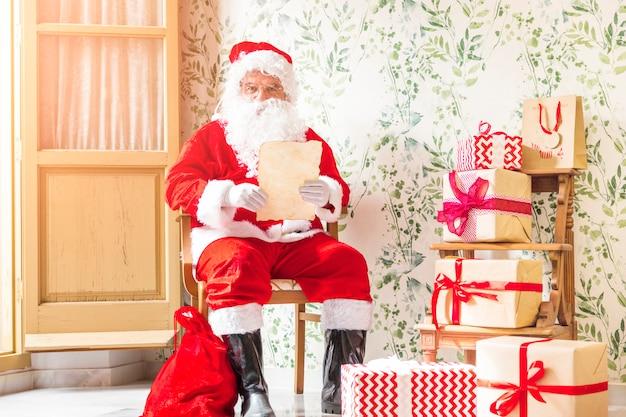Santa claus, die auf stuhl mit buchstaben sitzt
