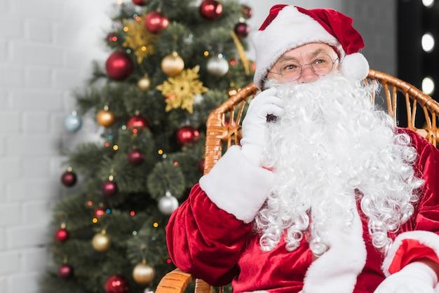 Santa claus, die auf stuhl sitzt und telefonisch spricht