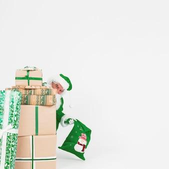 Santa claus, die aus geschenkboxen heraus schaut