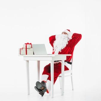 Santa claus, die bei tisch auf stuhl stillsteht