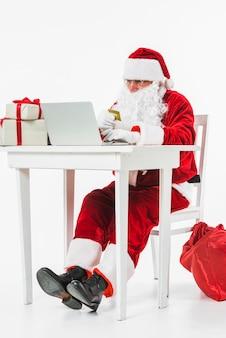 Santa claus, die bei tisch mit kreditkarte sitzt