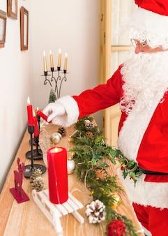 Santa claus, die beleuchtete kerze hält