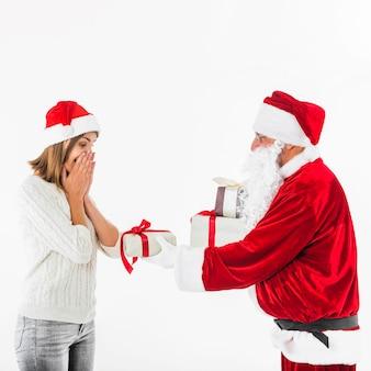 Santa claus, die der frau geschenkbox gibt