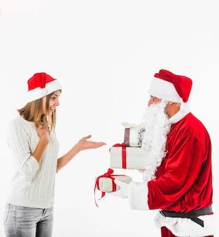 Santa claus, die der jungen frau geschenkbox gibt