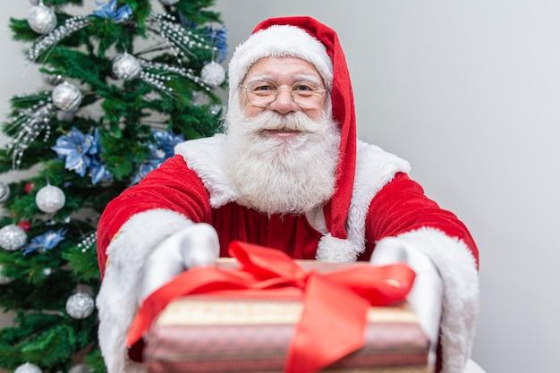 Santa claus, die der kamera ein geschenk anbietet