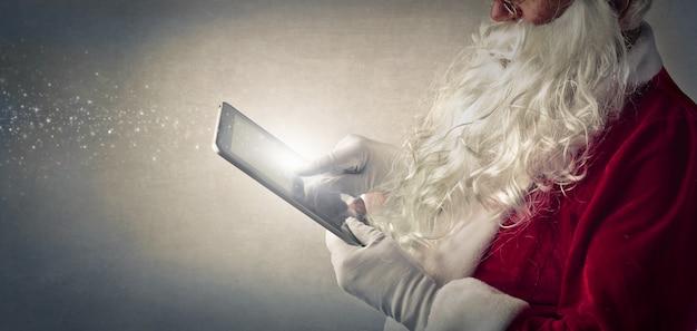 Santa claus, die eine tablette verwendet