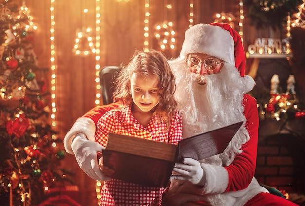 Santa claus, die einem kleinen netten mädchen ein geschenk gibt