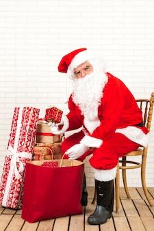 Santa claus, die geschenk hält und auf stuhl sitzt