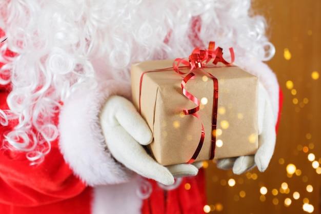 Santa claus, die geschenkbox gegen unscharfe weihnachtslichter hält