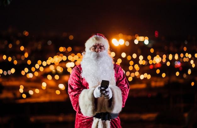 Santa claus, die handy nachts verwendet