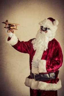 Santa claus, die hölzernes flugzeug der weinlese gegen schmutzwandhintergrund hält. weihnachtsferienkonzept
