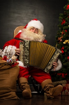 Santa claus, die im lehnsessel nahe weihnachtsbaum sitzt