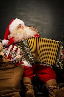 Santa claus, die im lehnsessel spielt musik auf akkordeon sitzt