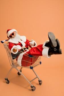 Santa claus, die im warenkorb sitzt und das zeichen super zeigt
