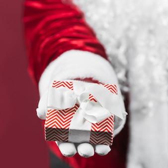 Santa claus, die in der hand geschenkbox hält