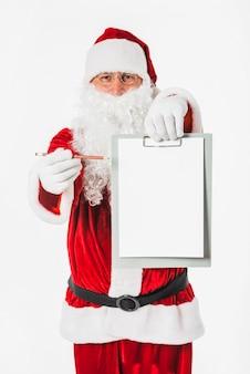 Santa claus, die in der hand leeres klemmbrett hält