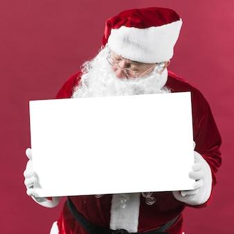 Santa claus, die leeres weißbuch in den händen hält