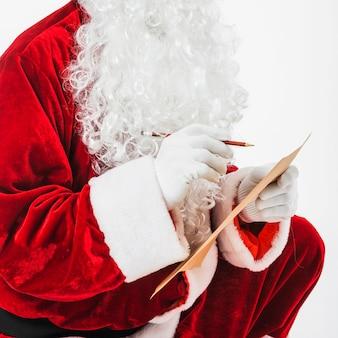 Santa claus, die mit kinderliste sitzt