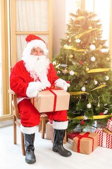 Santa claus, die nahe weihnachtsbaum mit geschenk sitzt