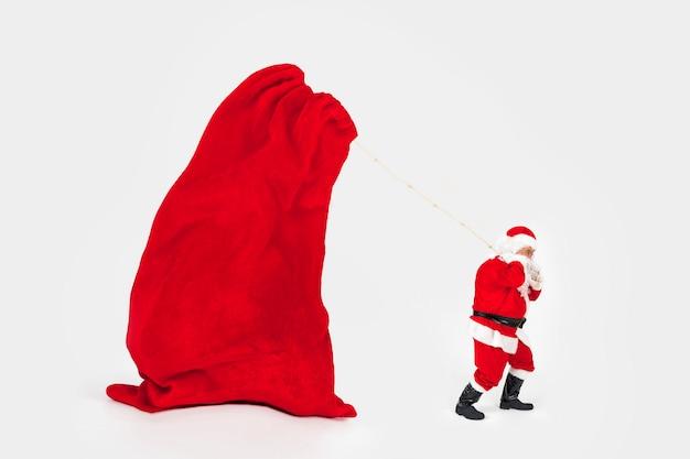 Santa claus, die riesige tasche des neuen jahres schleppt