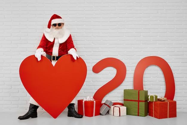 Santa claus, die rotes papierherz bei der aufstellung an der kamera hält