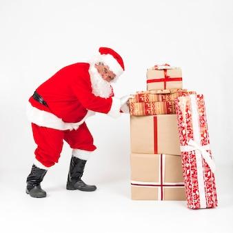 Santa claus, die stapel von eingewickelten geschenken drückt