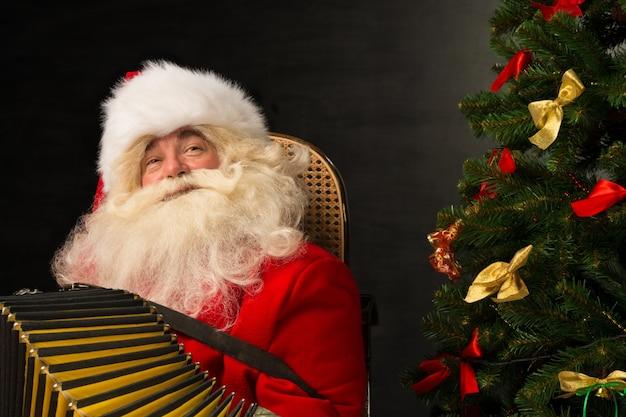 Santa claus, die zu hause im lehnsessel nahe weihnachtsbaum sitzt und musik auf akkordeon spielt
