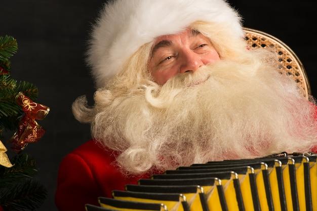 Santa claus, die zu hause im lehnsessel sitzt und musik auf akkordeon spielt