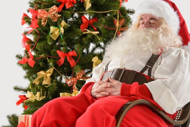 Santa claus, die zu hause im schaukelstuhl nahe weihnachtsbaum und im schlafen sitzt