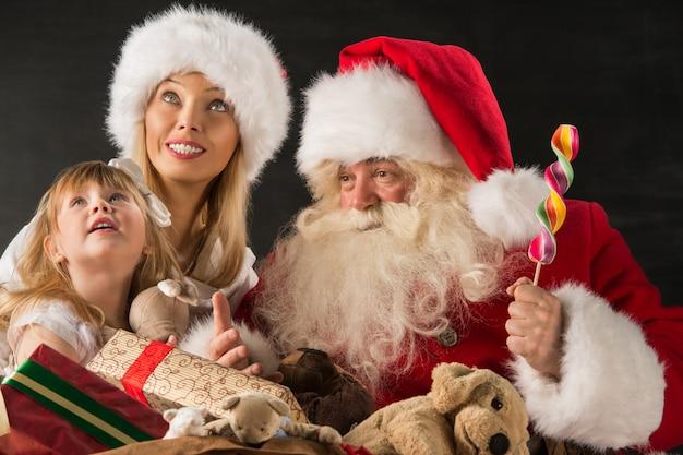 Santa claus, die zu hause mit familie sitzt
