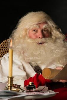 Santa claus, die zu hause sitzt und alte papierrolle liest